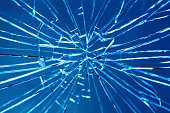 Smashed window with multiple cracks against blue background