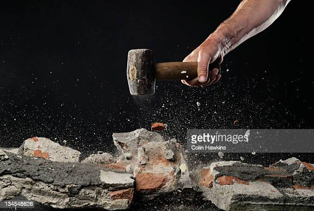 Smashing brick work with hammer