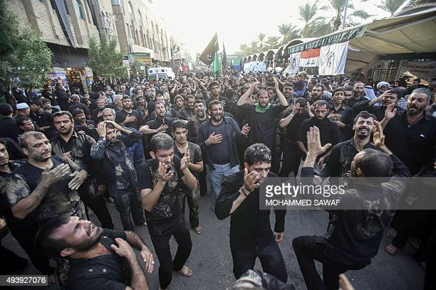 Smeared with mud Iranian Shiite Muslim pilgrims beat their chests as they take part in a parade in preparation for the peak of the Ashura ceremony in...