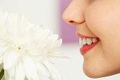 Young woman enjoying tender fragrance of white chrysanthemum