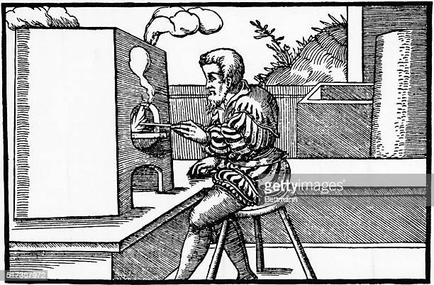 1556 Smelting furnace from Agricola's 'De Re Metallica' Engraving shows man seated before a furnace
