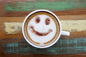 Smile face drawing on latte art coffee , wood color background