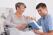 Smiled senior woman on wheelchair smiling to her nurse, who is reading a book