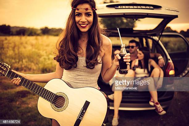 Smiley country guitarist on a rural road