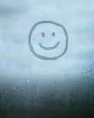 Smiley face drawn over condensated glass in a winter atmosphere sensation
