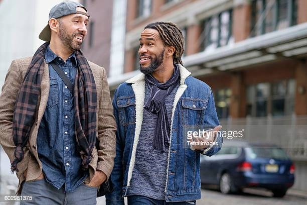 Smiley homosexual couple walking down street