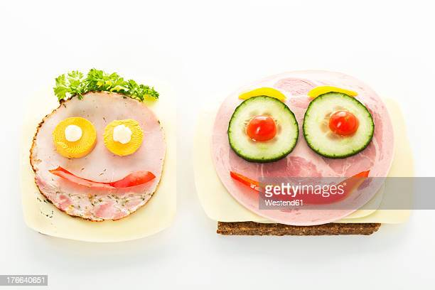 Smiley sausage sandwich with cheese and pepper on white background