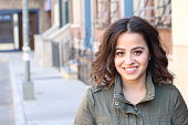 Closeup portrait, happy beautiful, smiling young woman in green jacket, posing on outdoors sidewalk, isolated on background with buildings, city urban life.