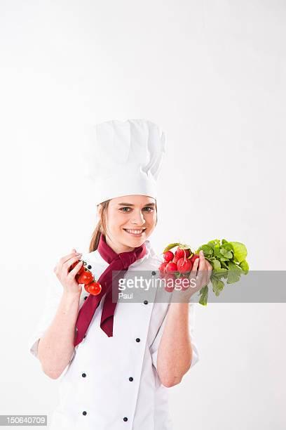 Smilig chef holding radish and tomatoes