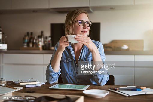 Smiliing woman drinking coffee while working online from home : Stock Photo