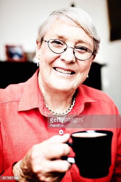 Smiling 70-plus woman holding coffee mug in her arthritic hand