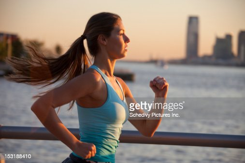 Smiling adolescent girl (18-21) running outdoors : Stock Photo