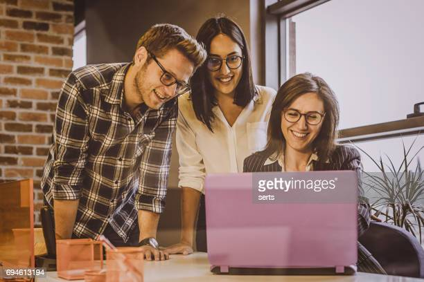 Smiling advisor businesswoman showing house pictures to young couple on laptop at office