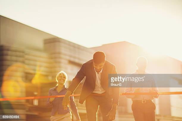 Smiling African American businessman crossing the finish line at sunset.