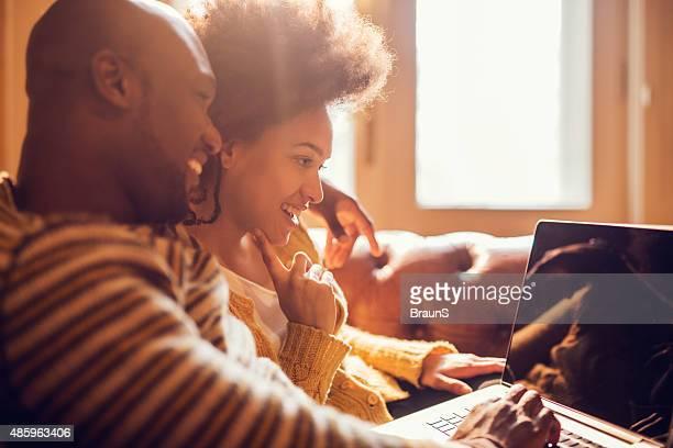 Sorridente coppia afro-americana, utilizzando un computer portatile a casa.