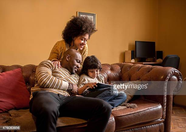 Smiling African American family using digital tablet at home.
