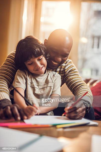 Smiling African American father and son coloring together.
