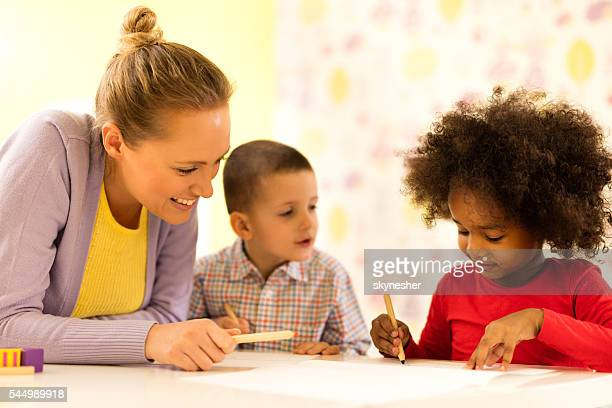 Smiling African American little girl and teacher writing at preschool.