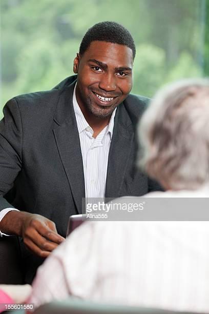 Souriant afro-américaine homme avec une femme âgée consulting