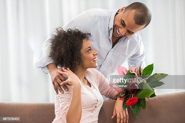 Smiling African American man surprising his wife with rose bouquet.
