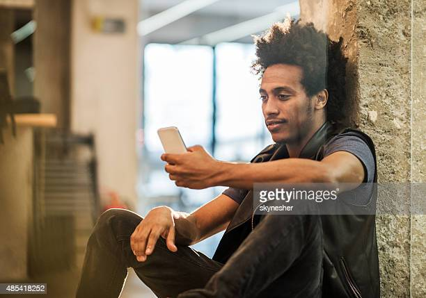 Smiling African American man text messaging on smart phone.