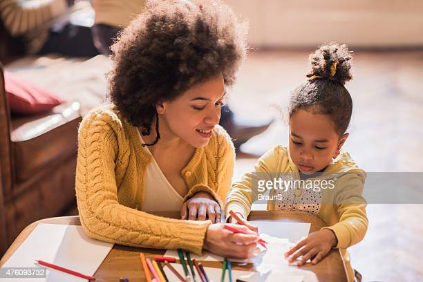 Smiling African American mother and daughter coloring together.