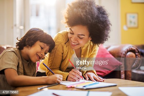 Smiling African American mother and son coloring together.