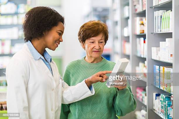 Smiling African American pharmacist assisting senior customer in a pharmacy.