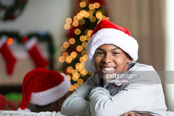 Smiling African American teenage boy wearing a Christmas Santa hat