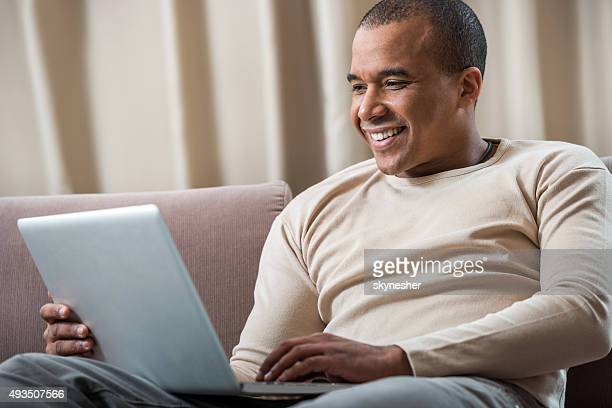 Smiling African American using laptop at home.