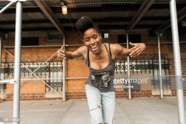 Smiling African American woman dancing under scaffolding
