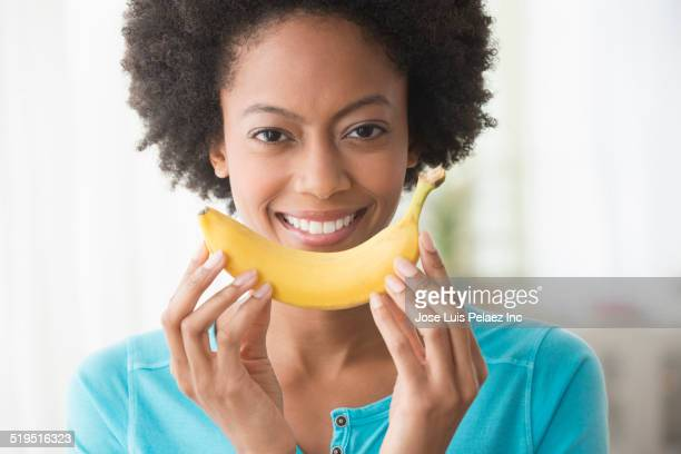 Smiling African American woman holding banana