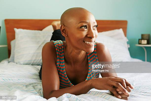 Smiling African American woman laying on bed
