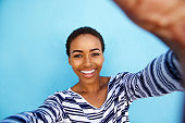Close up portrait of smiling african american woman taking selfie against blue wall