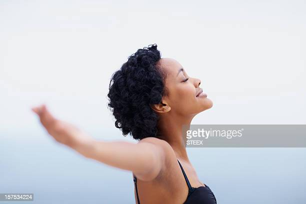Smiling African American young lady with arms outstretched