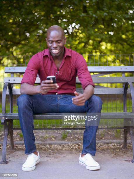 Smiling African man looking down at cell phone