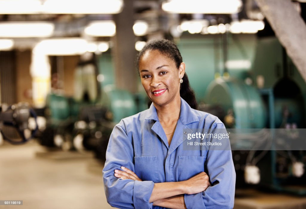 Smiling African technician with arms crossed in industrial plant