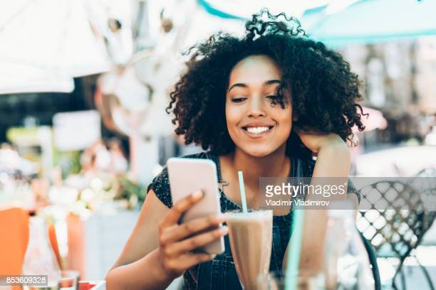 Smiling african woman drinking cocktail in cafeteria