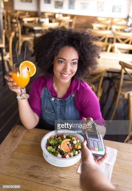 Smiling african woman drinking orange juice in cafeteria