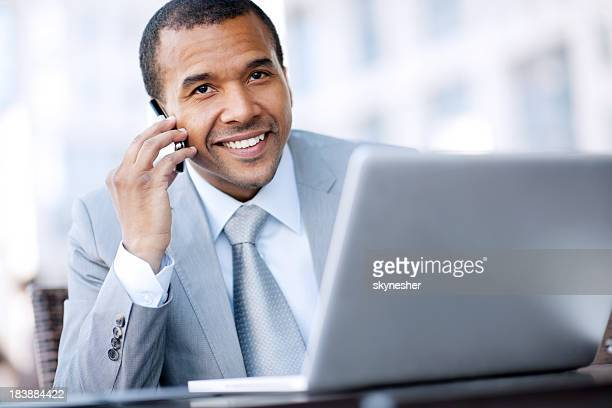 Smiling African-American businessman talking on a mobile phone.