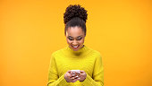 Smiling African-American woman chatting on smartphone, modern technology, app