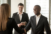 Happy smiling afro american businessman and caucasian businesswoman shaking hands standing in modern office, nice to meet you, first impression, congrats, promoted to the post, reward accomplishments