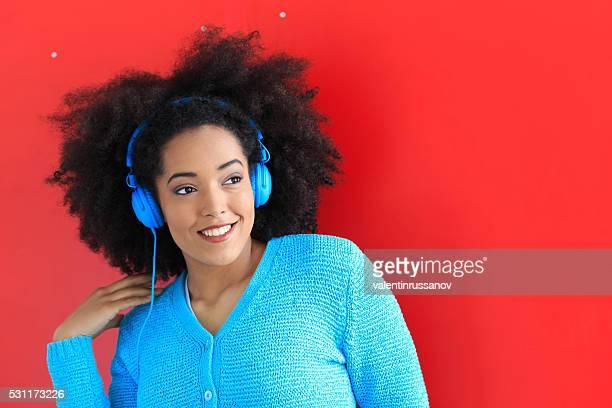 Sonriente mujer afro con auriculares azules