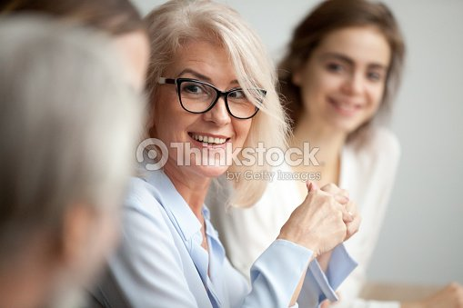 Smiling aged businesswoman looking listening to colleague at team meeting : Stock Photo
