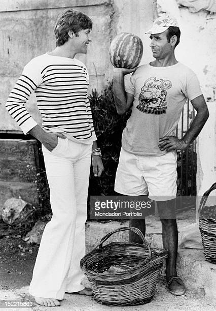 A smiling and barefoot Helmut Berger talks with a watermelons seller Taormina 1973