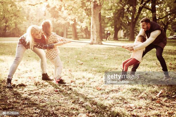 Smiling and cheerful family playing in park with rope.