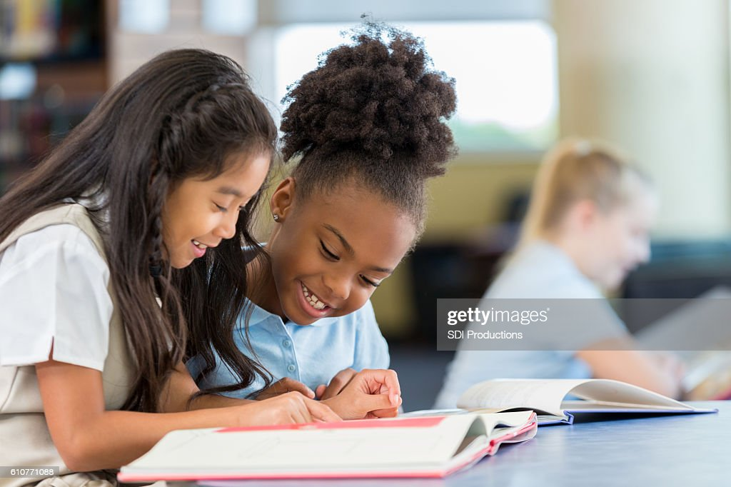 Smiling and cheerful schoolgirls reading a book together at school : Stock Photo