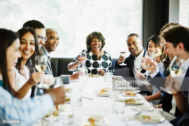 Smiling and laughing group of family and friends preparing to toast during celebration meal in restaurant