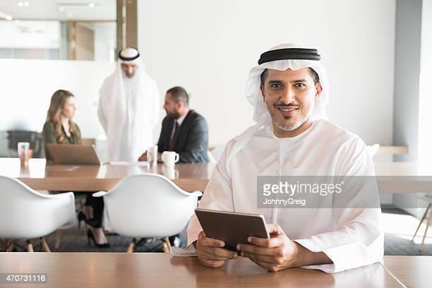 Smiling Arab businessman holding digital tablet in office