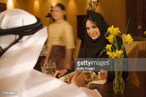 Smiling Arab Woman Looking Across Restaurant Table at Husband. Dubai, United Arab Emirates